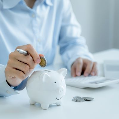 Businesswoman hand putting coin into piggy bank, step up start up business to success, Saving money for future plan and retirement fund concept.