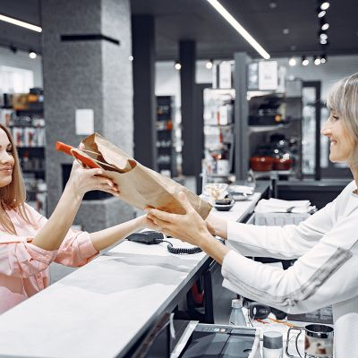 Woman examines various items of dishes. Beautiful woman shopping tableware in supermarket. Manager helps a costumer.