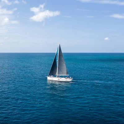 A snow-white yacht with bright sail t is sailing along the sea by, the backdrop of an azure sky.