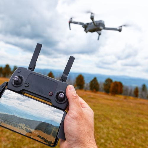 Landscaping on a quadrocopter. A young man holds in his hand a quadrocopter control panel with a monitor and an image of mountains; in the background is a quadrocopter