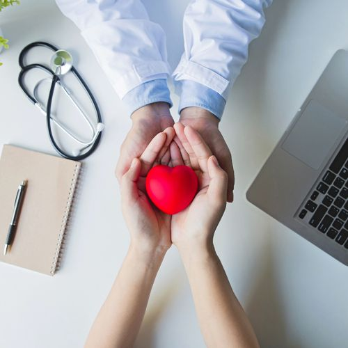 Top view .doctor and patient hands holding red heart on white table, health care love, give, hope and family concept, world heart day,world health day